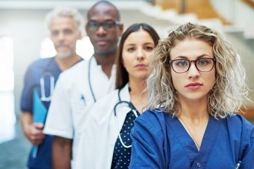 Pensive team of doctors looking at camera standing in a hospital.